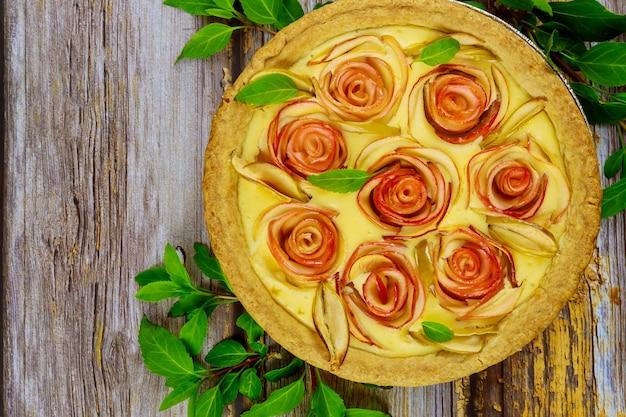 Tarte aux pommes fraîche avec décoration comme une rose sur une surface en bois. vue de dessus.