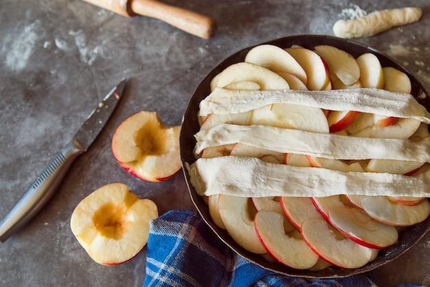 Tarte aux pommes avec des fruits coupés en deux sur la table