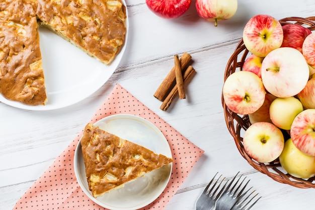 Tarte aux pommes maison avec cannelle et pommes mûres fraîches en arrière-plan