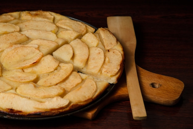 Tarte aux pommes maison et morceau de tarte avec des tranches de pomme à la table de cuisson.