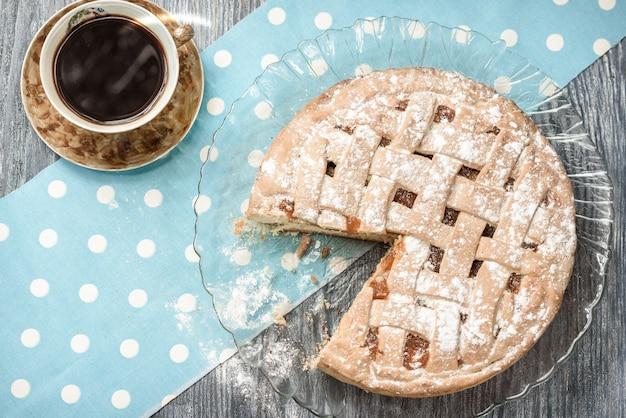 Tarte aux pommes maison avec une tasse de café sur une table en bois gris.