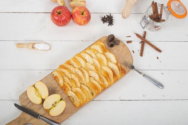 Tarte aux pommes avec pâte à brioche sur planche à découper en bois. vue de dessus.