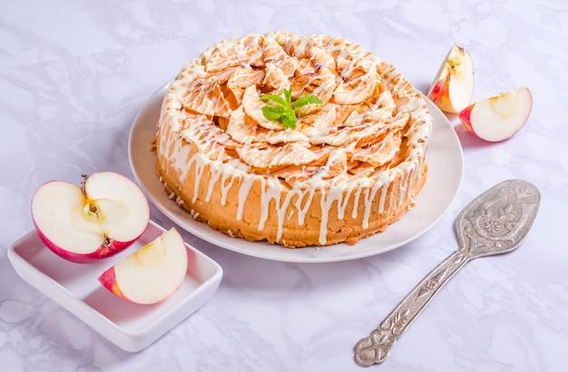 Tarte aux pommes avec pâte brisée et glaçage blanc sur une assiette sur fond clair