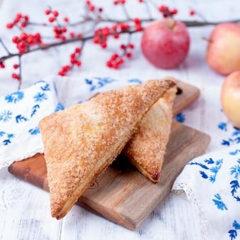 Tarte aux pommes sur une planche de bois et sur un fond blanc