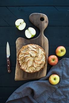 Tarte aux pommes sur une planche à découper sombre sur fond de bois noir, vue de dessus.