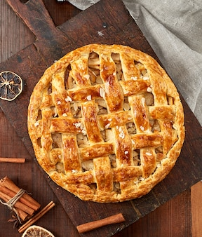 Tarte aux pommes ronde au four sur une planche de bois brune