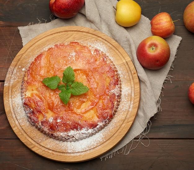 Tarte aux pommes ronde au four sur planche de bois et pommes fraîches