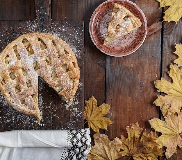 Tarte aux pommes ronde cuite au four et un morceau coupé sur une assiette