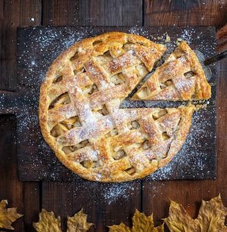 Tarte aux pommes ronde et cuite au four sur une vieille planche à découper brune saupoudrée de sucre en poudre