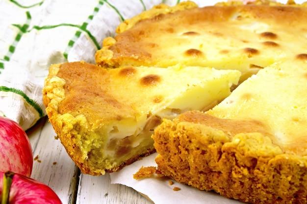 Tarte aux pommes avec sauce à la crème sure sur un parchemin, fruits, serviette sur fond de planche de bois