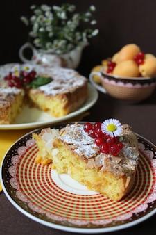 Tarte aux pommes saupoudrée de sucre en poudre et décorée de groseilles rouges