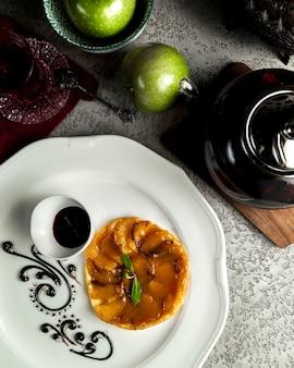 Tarte aux pommes servie avec du sirop de fruits