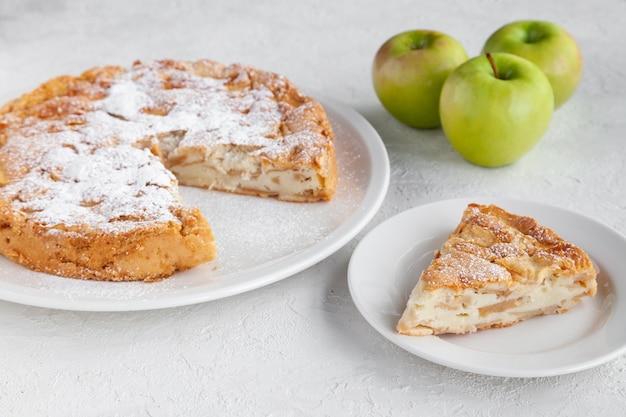 Tarte aux pommes sucrée maison charlotte et morceau de gâteau près de la plaque, copiez l'espace, place pour le texte, vue d'en haut