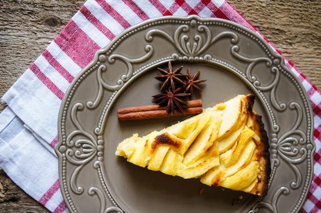Tarte aux pommes avec une tasse de café sur une table en bois