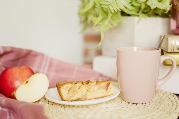 Tarte aux pommes, tranches de pomme et une tasse de thé avec du lait sur la table.