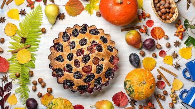 Tarte aux prunes sur un fond d'automne clair, avec des feuilles mortes, fruits, noix, citrouille. lay plat.