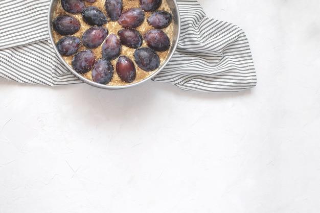 Tarte aux prunes non cuite dans un moule en métal sur une serviette à rayures froissée.