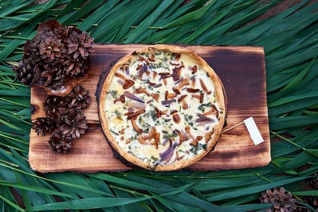 Tarte aux quiches maison avec champignons (girolles) et fromage à bord, vue du dessus. tarte salée aux champignons.