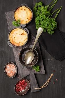 Tarte de berger, cocotte anglaise dans une poêle en fonte, avec viande hachée, purée de pommes de terre et légumes