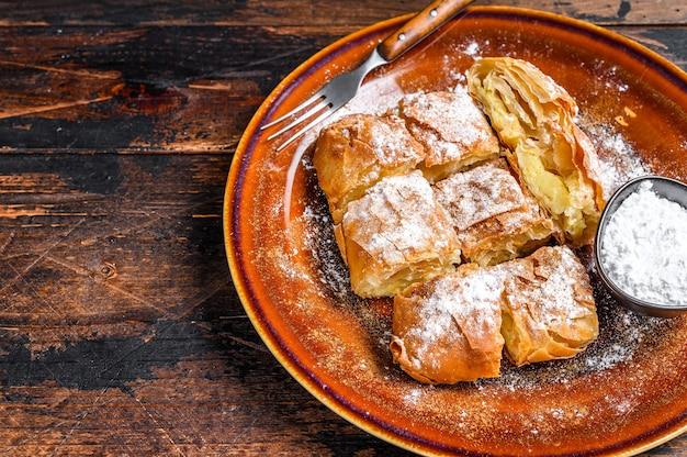 Tarte bougatsa grecque tranchée avec pâte phyllo et crème à la semoule. sombre