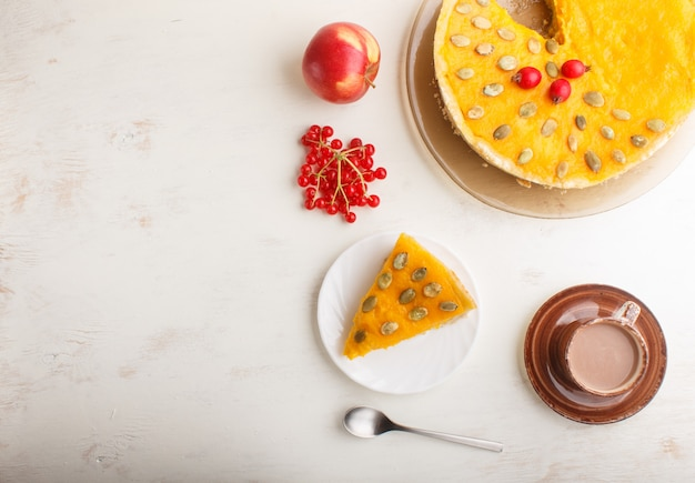 Tarte à la citrouille américaine traditionnelle décorée avec des baies rouges aubépine et des graines de citrouille avec une tasse de café sur un bois blanc. vue de dessus.