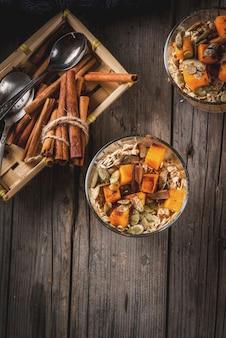 Tarte à la citrouille épicée nuit gruau à la cannelle, l'anis et le sirop d'érable sur la vieille table rustique en bois