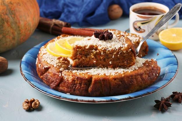 Tarte à la citrouille maison au citron, cannelle et noix, saupoudrée de noix de coco, tranchée, sur fond bleu clair avec une tasse de café