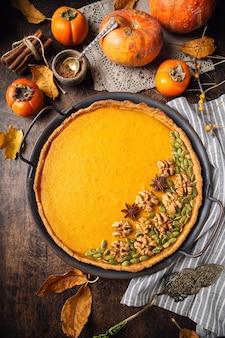 Tarte à la citrouille maison fraîche pour thanksgiving décorée de noix et de graines au plateau vintage sur fond de contreplaqué rustique. vue de dessus.