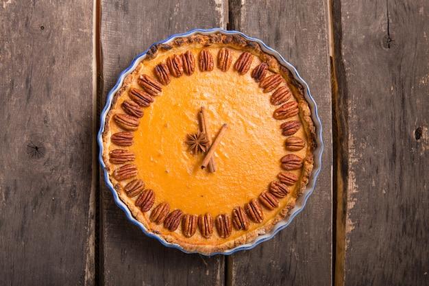 Tarte à la citrouille avec noix de pécan et cannelle sur fond rustique. pâtisserie d'automne maison pour thanksgiving