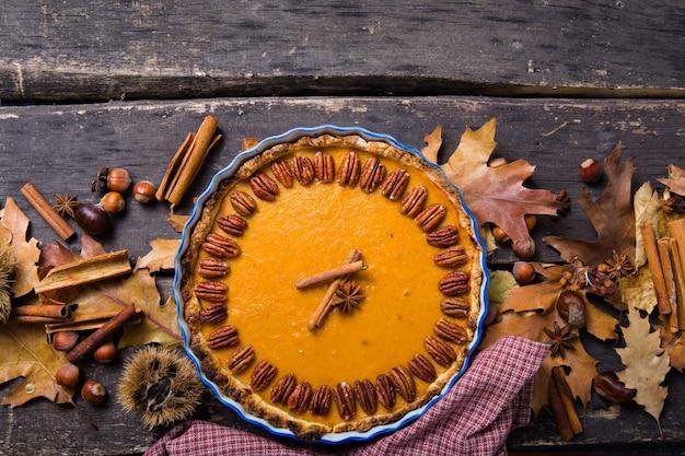Tarte à la citrouille avec noix de pécan et cannelle sur fond rustique, vue de dessus, copiez l'espace. pâtisserie d'automne maison pour thanksgiving