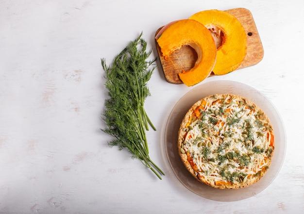 Tarte à la citrouille sucrée au fromage et à l'aneth sur fond de bois blanc