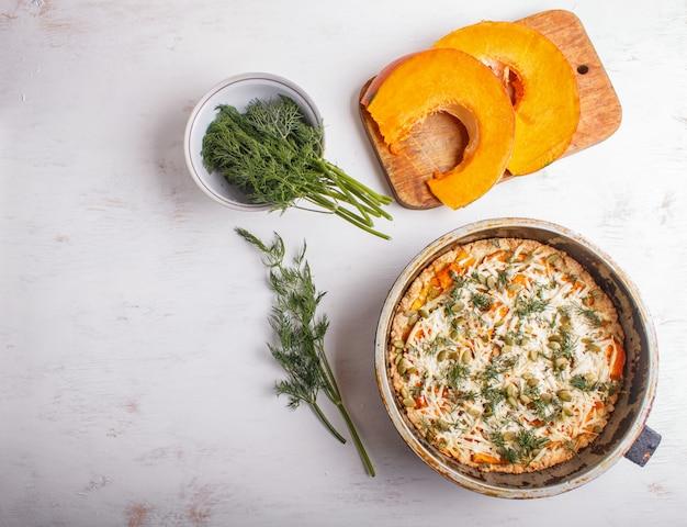 Tarte à la citrouille sucrée au fromage et à l'aneth sur un fond en bois blanc.