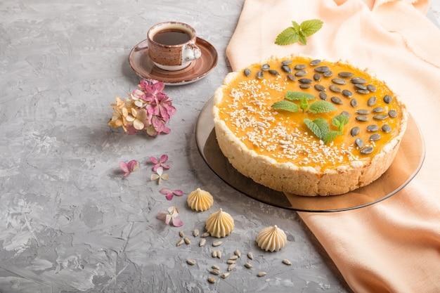 Tarte à la citrouille sucrée traditionnelle américaine décorée avec des graines de menthe, de sésame et de citrouille. vue de côté, copyspace.