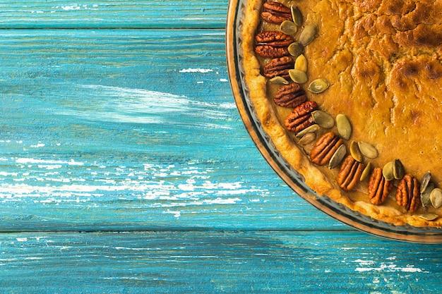 Tarte à la citrouille traditionnelle faite maison décorée de noix et de graines.
