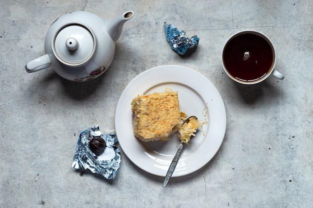 Tarte à la crème pâtissière feuilletée maison, chocolats, bouilloire et tasse