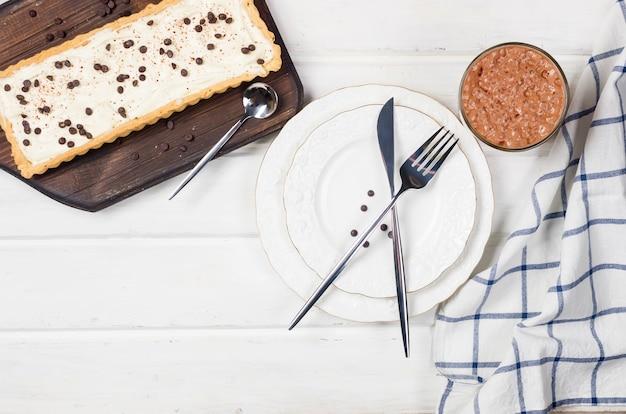 Tarte à la crème vanille ou cheesecake avec des gouttes de chocolat et tasse de café sur une table en bois blanc,