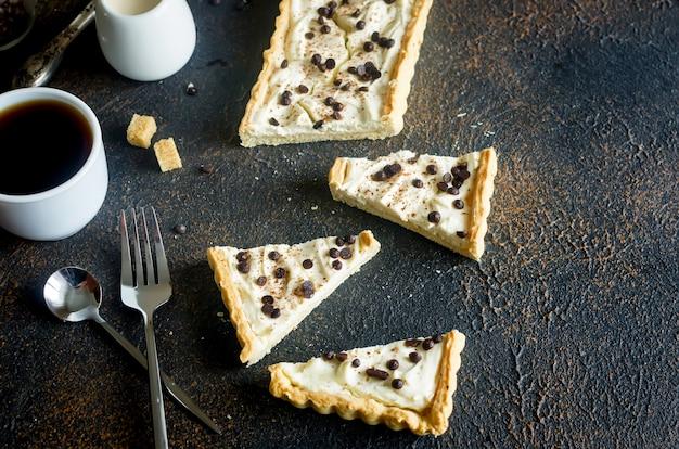 Tarte à la crème à la vanille ou cheesecake avec des gouttes de chocolat et une tasse de café