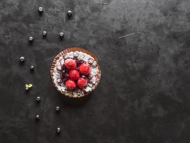 Tarte délicieuse, gâteaux de pâtisserie colorés bonbons aux framboises fraîches et myrtilles sur tableau noir.