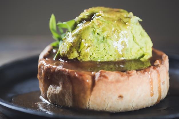 Tarte de gibier à la viande de canard dans un plat de service avec purée de petits pois et feuilles d'épinard se bouchent