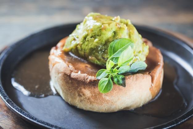 Tarte de gibier à la viande de canard dans un plat de service avec purée de pois et feuilles d'épinard se bouchent