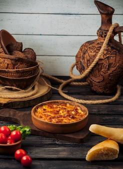 Tarte à l'intérieur du bol en poterie avec du pain et des tomates.