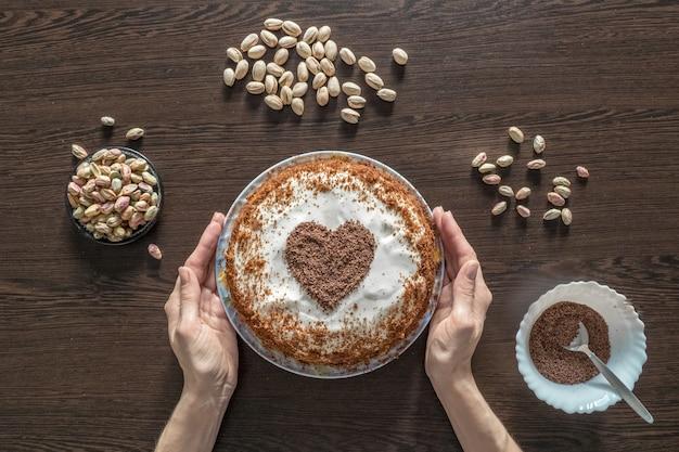 Tarte à la main avec glaçage au fromage à la crème et un cœur au chocolat. bonbons pour la saint-valentin