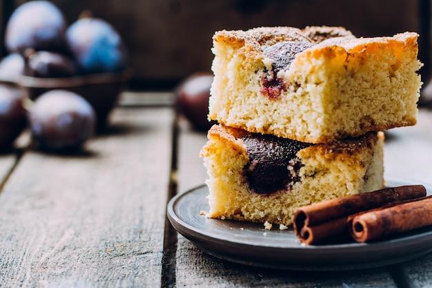 Tarte maison aux prunes sur le fond de la table en bois. gâteau d'automne aux fruits à la cannelle.