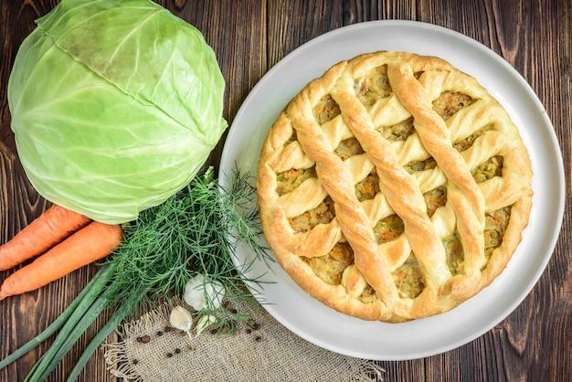 Tarte maison avec chou, carotte, oignon et viande sur bois