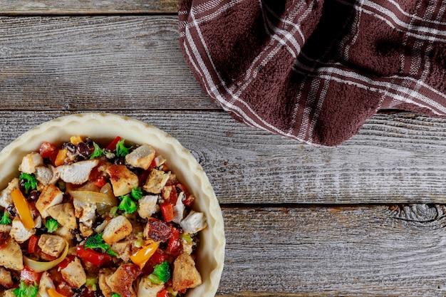 Tarte maison fraîche de viande de poulet tarte fermée sur la table en bois servie de légumes