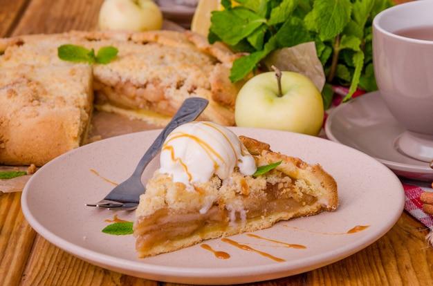 Tarte ouverte ou galette aux pommes avec cannelle et miettes servies avec une tasse de thé chaud et une boule de glace à la vanille