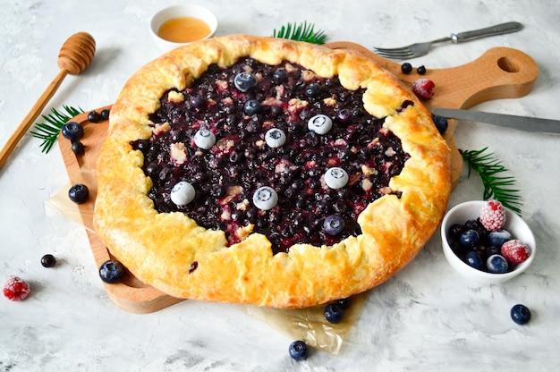 Tarte ouverte ou galette avec des baies, des couverts et des baies fraîches sur une table concept alimentaire sain. nourriture rustique.