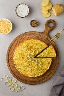 Tarte à la quiche avec pommes de terre aux poireaux et fromage à plat sur fond gris sur une planche à découper en bois ronde