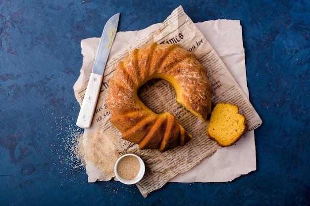 Tarte ronde à la citrouille, sur papier kraft, couteau, saucière, cassonade, morceau de gâteau, vue de dessus, fond bleu foncé
