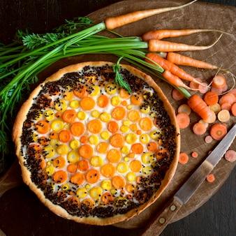 Tarte rustique aux carottes. sur un fond sombre.